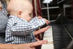 Beautiful little baby boy plays piano Royalty Free Stock Image