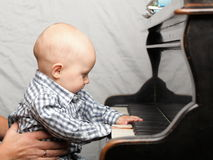 Beautiful little baby boy plays piano Royalty Free Stock Images