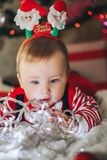 Beautiful little baby boy in Santa hat celebrates Christmas and play with garland. New Year`s holidays. Toddler with gift in the royalty free stock photography