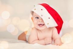Beautiful little baby celebrates Christmas New Year`s holidays Baby red hat boken background stock photo