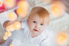 Beautiful little baby celebrates Christmas. New Year`s holidays. Sweet baby girl in cute dress having fun in festive. Decorated room royalty free stock images