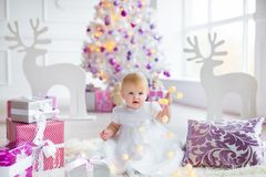 Beautiful little baby celebrates Christmas. New Year`s holidays. Sweet baby girl in cute dress having fun in festive Royalty Free Stock Image