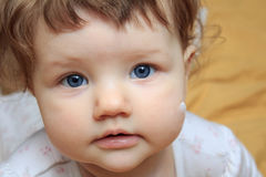 Beautiful little baby with the cream on the skin of the cheeks. stock image