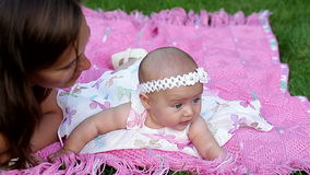 Beautiful little baby girl with her mother lying on a pink blanket stock video