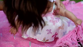 Beautiful little baby girl with her mother lying on a pink blanket stock footage