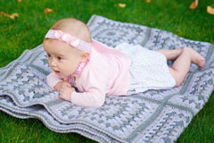 Beautiful little baby girl is lying on a plaid blanket Stock Image