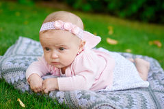 Beautiful little baby girl is lying on a plaid blanket Stock Images