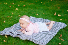 Beautiful little baby girl is lying on a plaid blanket Stock Photography