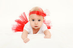Beautiful little baby girl lying in red skirt Stock Images