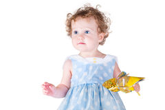 Beautiful little baby girl playing with a wind toy. Wearing a nice dress Royalty Free Stock Image
