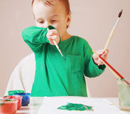 Beautiful little baby girl in the process of drawing (postmodern Stock Photo