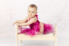Beautiful little baby girl sitting on the bed wearing pink dress Stock Photography