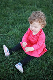 Beautiful little baby girl sitting on a green meadow Royalty Free Stock Image
