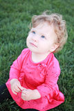Beautiful little baby girl sitting on a green meadow Royalty Free Stock Photos