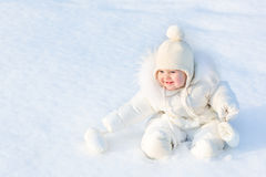 Beautiful little baby girl sitting in white snow Royalty Free Stock Images