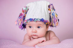 Beautiful little baby girl wearing pink knitted cap.  Stock Photos