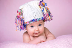 Beautiful little baby girl wearing pink knitted cap.  Royalty Free Stock Photo
