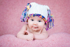 Beautiful little baby girl wearing pink knitted cap.  Royalty Free Stock Photography