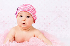 Beautiful little baby girl wearing pink knitted cap. Studio portrait of cute funny baby girl Royalty Free Stock Photos