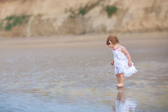 Beautiful little baby girl wearing white dress on beach Royalty Free Stock Photos