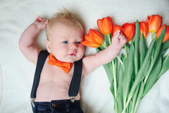 Beautiful little baby lying near tulips Stock Images