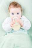 Beautiful little baby with a milk bottle under knitted blanket Stock Photos