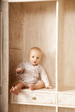 Beautiful little baby sitting in the closet. Smiling child and i Stock Photography