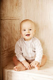 Beautiful little baby sitting in the closet. Smiling child and i Royalty Free Stock Images