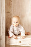 Beautiful little baby sitting in the closet. Smiling child and i Royalty Free Stock Photo