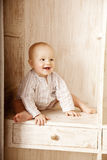 Beautiful little baby sitting in the closet. Smiling child and i Royalty Free Stock Photography