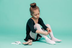 Beautiful little ballerina in black dress for dancing puting on foot pointe shoes Royalty Free Stock Photo