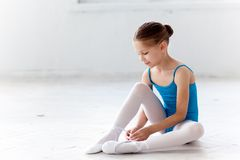 Beautiful little ballerina in blue dress for dancing puting on foot pointe shoes Royalty Free Stock Photos