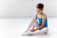 Beautiful little ballerina in blue dress for dancing puting on foot pointe shoes Stock Photography