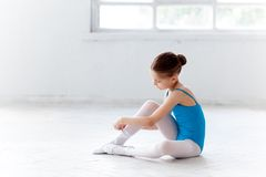 Beautiful little ballerina in blue dress for dancing puting on foot pointe shoes Stock Photo