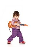 Beautiful little bliss girl plays with a guitar Royalty Free Stock Photography