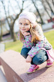 Beautiful little blond girl with blue eyes having fun sitting or playing on spring or autumn outdoors happy smiling Royalty Free Stock Image