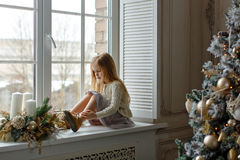 Beautiful little blond girl with blue eyes sitting on the window. And smiling at the New Year on the background of the Christmas tree royalty free stock image