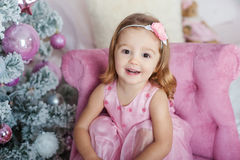 Beautiful little blond girl with brown eyes smiling at the New Year on the background of the Christmas tree stock photo