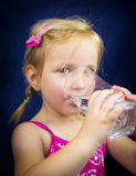 Beautiful little blond girl drinking water Royalty Free Stock Images