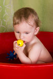 Beautiful little blond girl sitting in the bathroom and chew toys Stock Photos