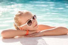 Beautiful little blond girl with sunglasses in pool Stock Photos