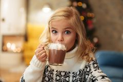 Beautiful little blonde girl drinking cacao with marshmallow on. Christmas morning, looking at camera Royalty Free Stock Image