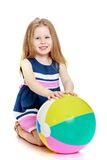 Beautiful little blonde girl with a large. Inflatable ball-isolated on white background Stock Image