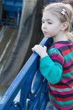 Beautiful little blonde girl near the blue old railing Stock Image