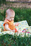 Beautiful little blonde girl sitting on a meadow Stock Photo