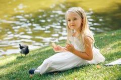 Beautiful little blonde girl sitting near river and feeding pigeons stock photo