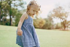 Beautiful little blonde girl walking in the Park Stock Photos