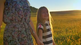 Beautiful little blonde girl walking in wheat field and looking at mother, holding hands and smiling, pointing at sunset stock video