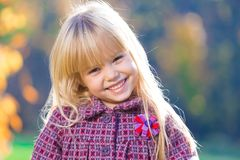 Face, fun, close up. Beautiful little blonde hair girl, has fun smile face, happy brown eyes, white teeth. Child portrait. Creative concept. Autumn time. Close royalty free stock images