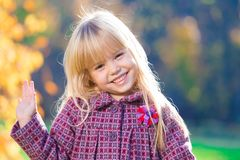Face, fun, close up. Beautiful little blonde hair girl, has fun smile face, happy brown eyes, white teeth. Child portrait. Creative concept. Autumn time. Close royalty free stock photos